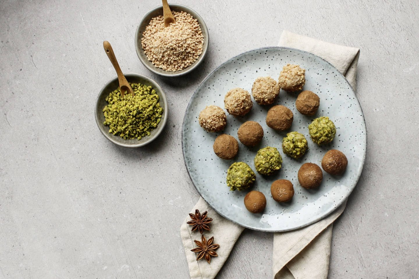 Marzipan balls with bourbon vanilla sugar on a light blue plate with 2 bowls full of pistachios and hazelnut brittle