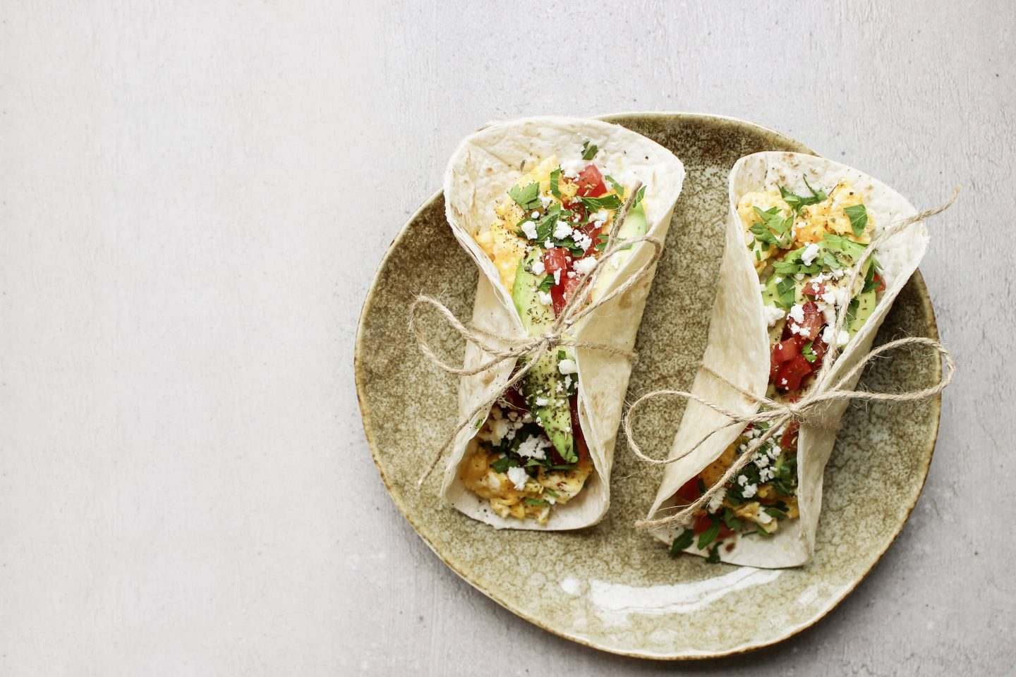 Breakfast tacos with herbs Rustikana on a beige plate tied with a thread