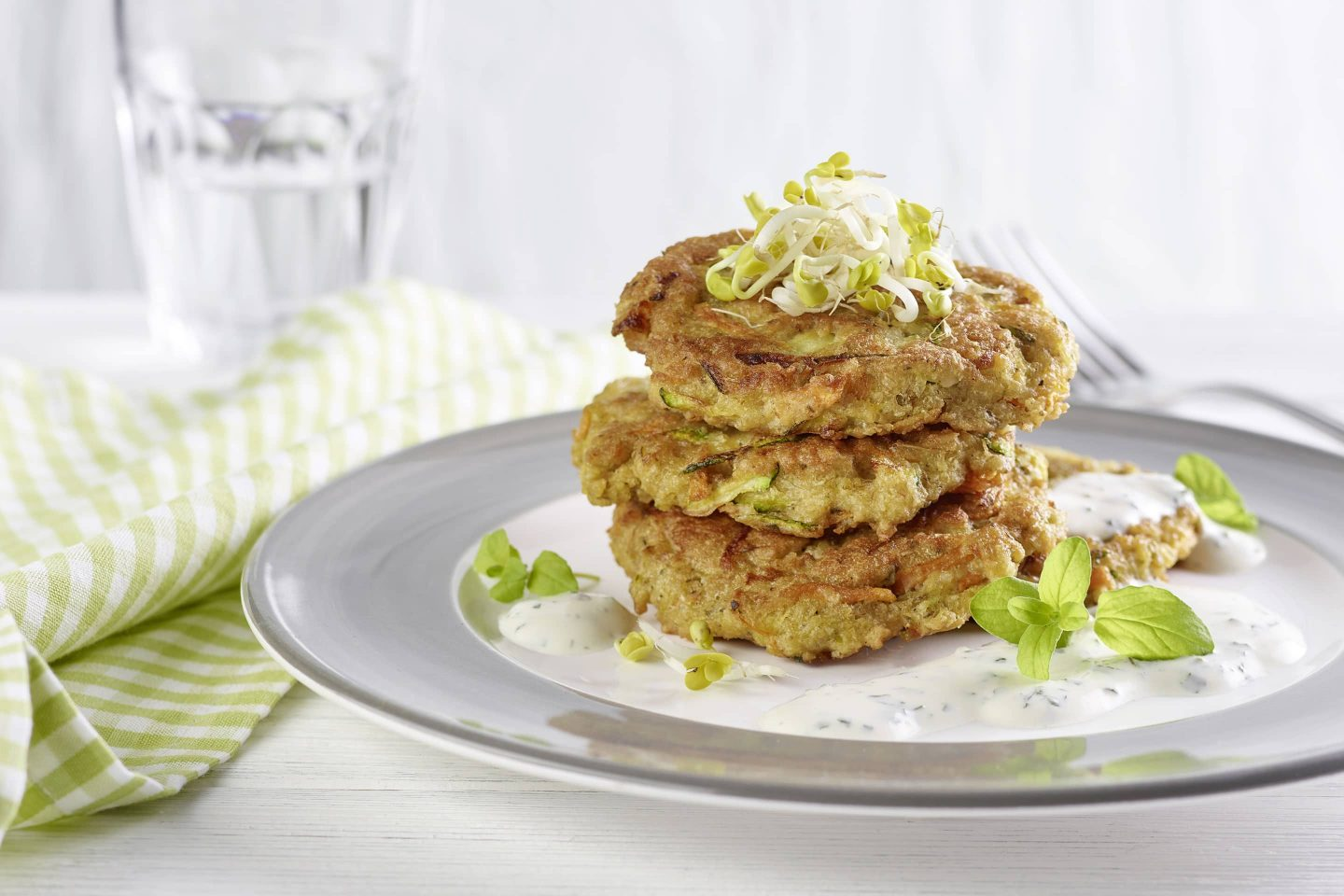 Carrot and zucchini patties with oatmeal and marjoram prepared on a plate with a gray rim and a green checkered napkin