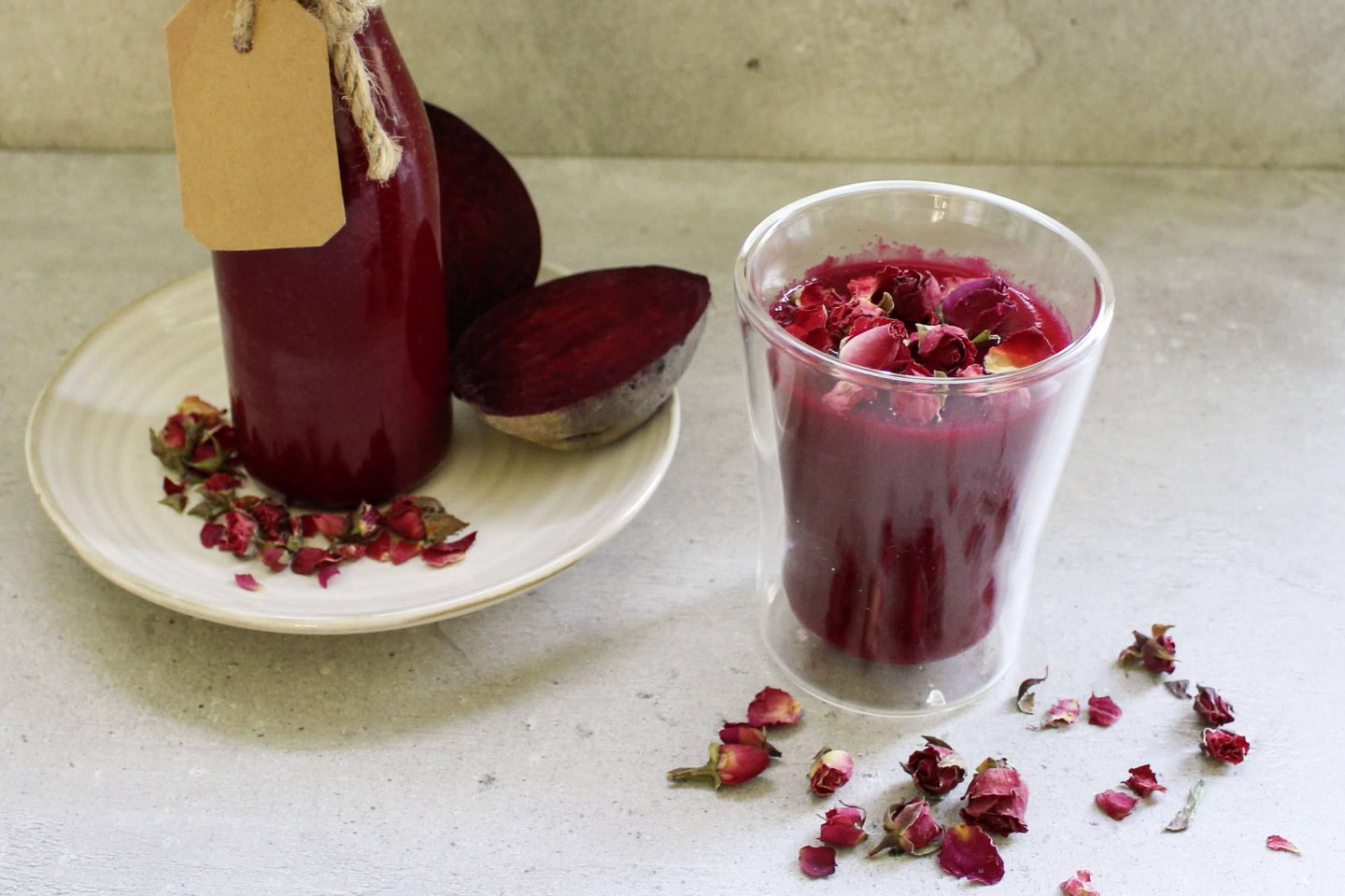 Beetroot smoothie with ground ginger in a glass garnished with rose petals