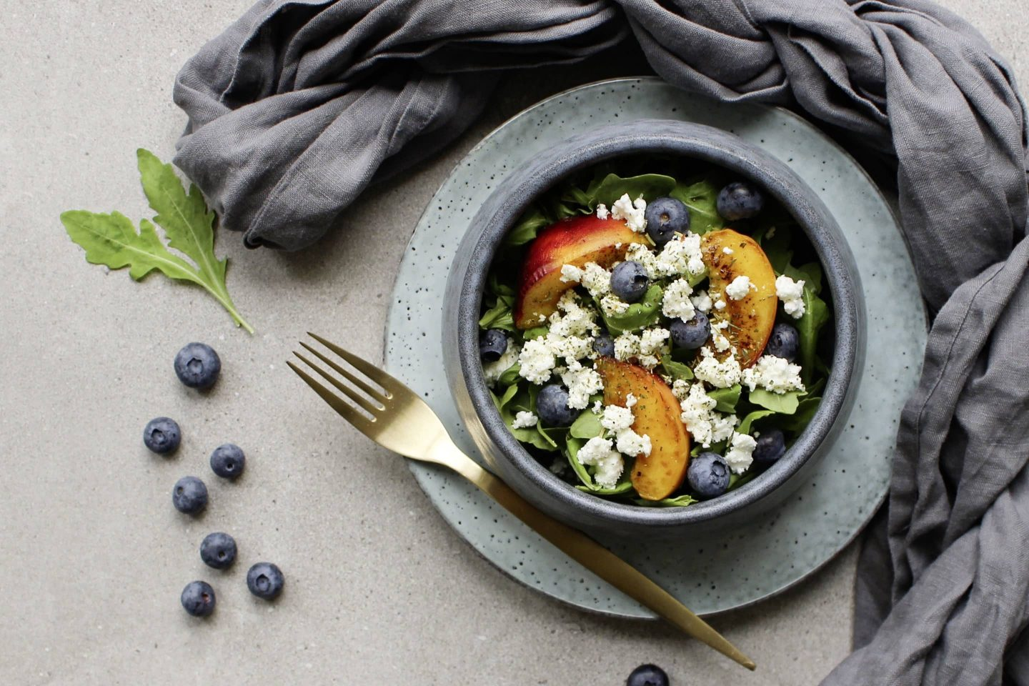 Salad with crumbled goat cheese, fresh blueberries and peach in a light blue bowl