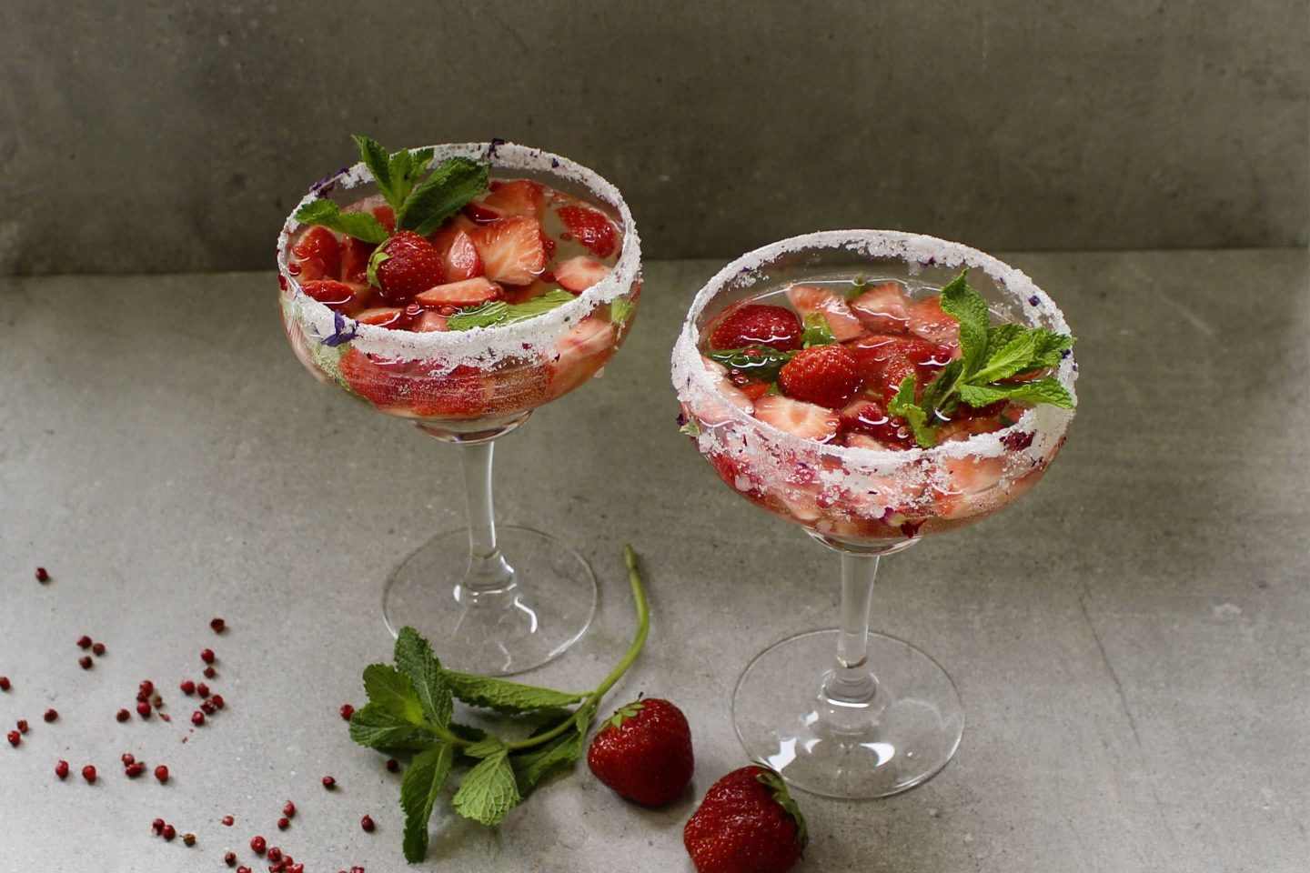 Summer punch with pink berries and fresh strawberry pieces in sugar-coated cocktail glasses, garnished with fresh mint