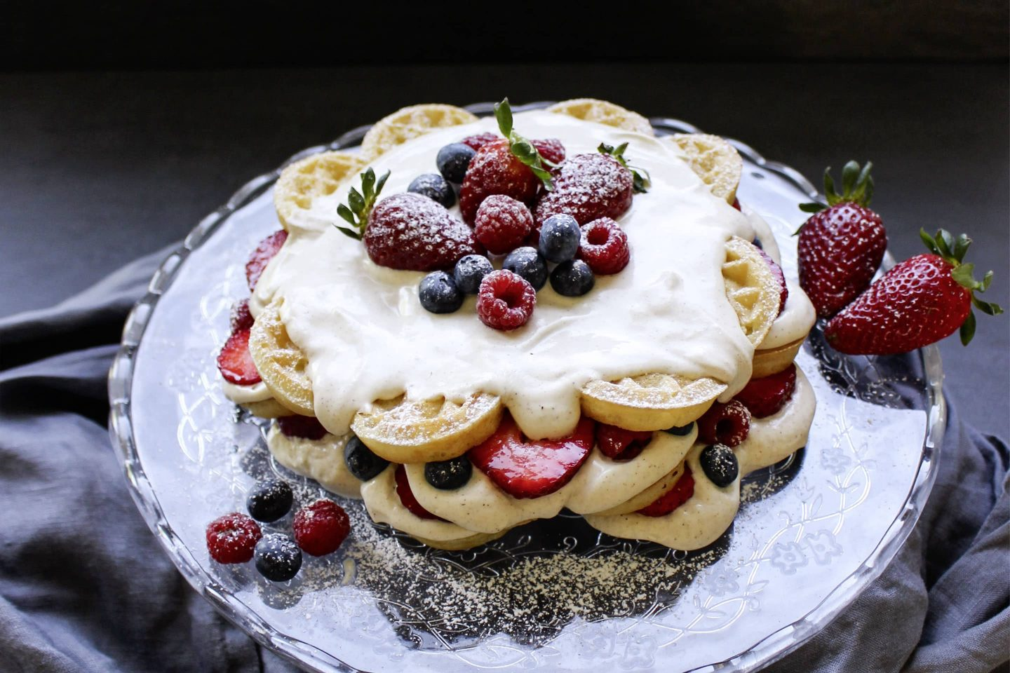 Wafflecake with fresh berries on a glass cake stand