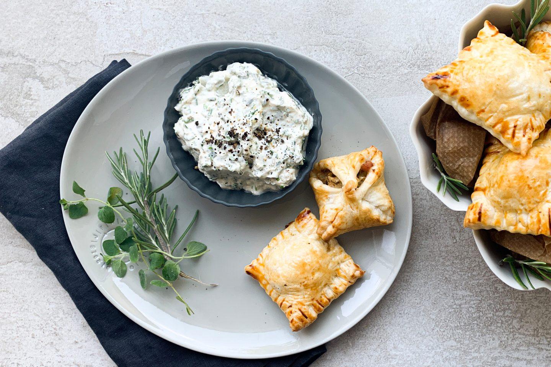 filled cabbage pastry Gefüllte Speck-Kraut-Taschen auf einem Teller mit Dip und frischen Kräutern