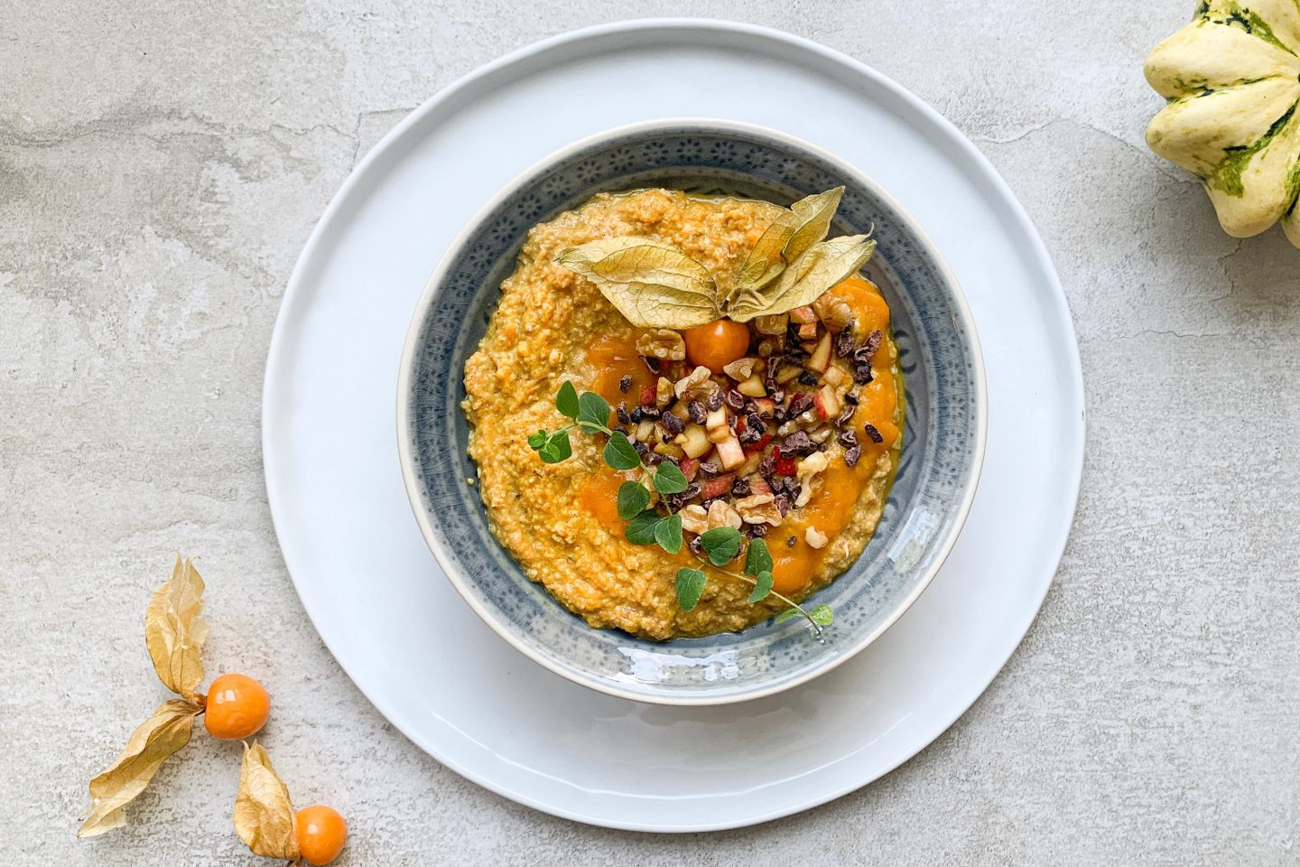 golden pumpkin porridge placed in a lightblue bowl and topped with apple pieces and nuts