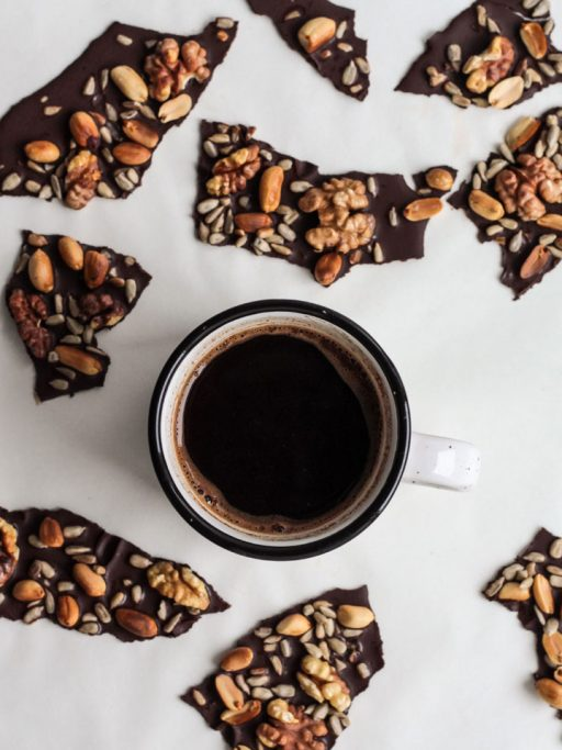 a cup of coffee in the middle of chocolate pieces on a white surface