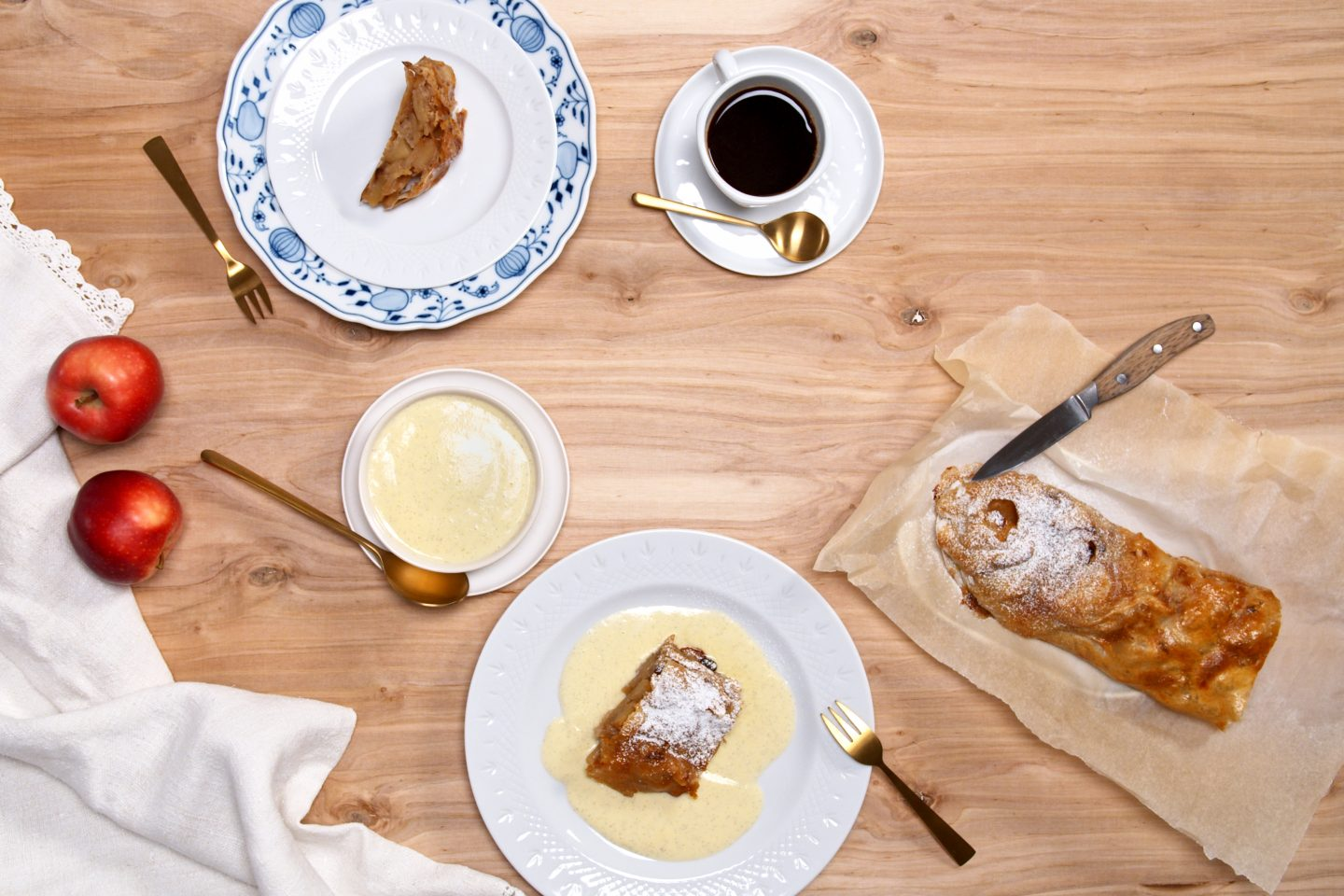 Apple strudel With vanilla sauce on 2 plates, served with coffee and the remaining apple strudel on baking paper