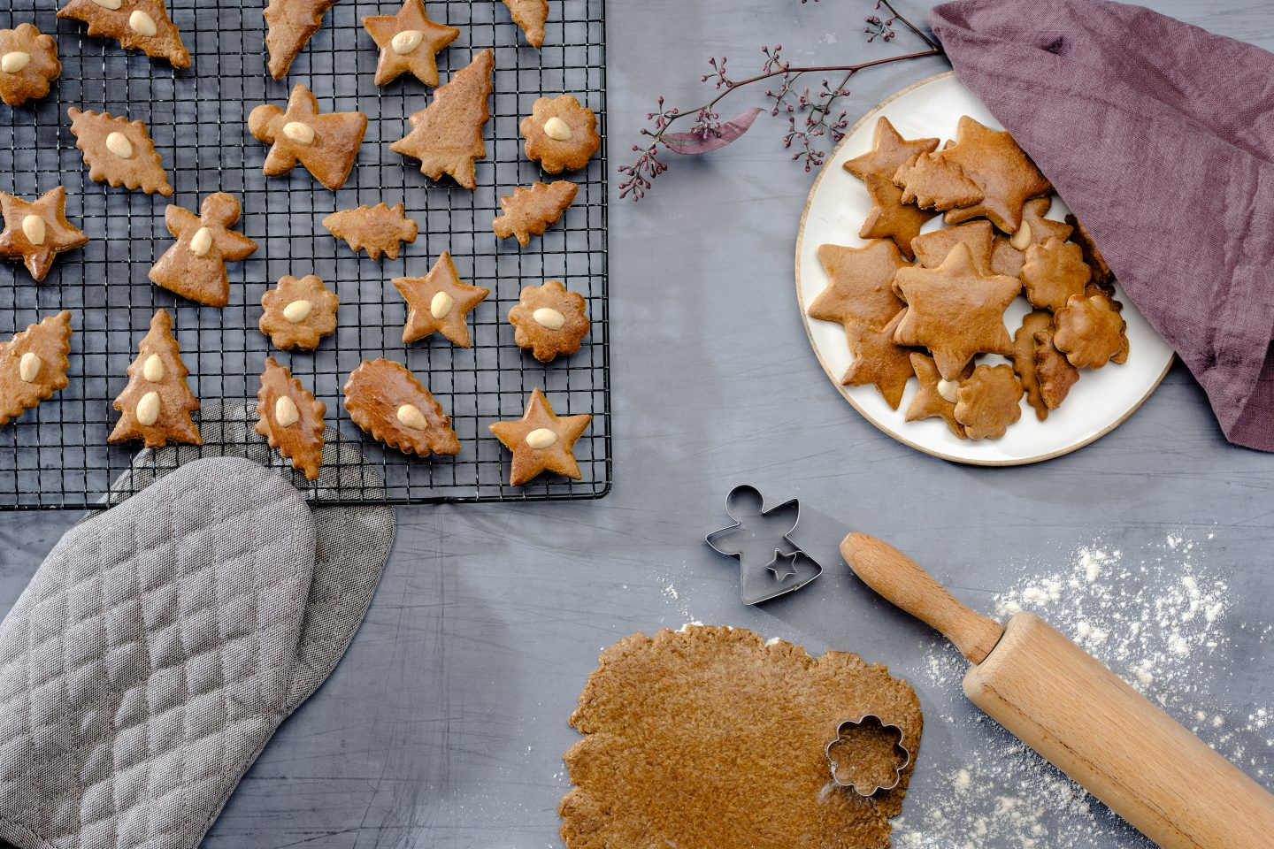 Honey gingerbreads are being cut out of dough and lie on a black wire rack to cool down