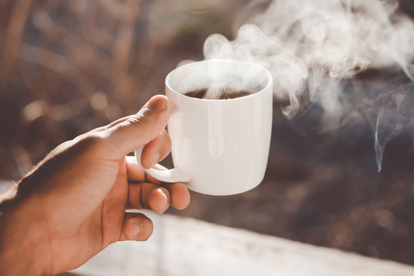 a hand is holding a cup of coffee