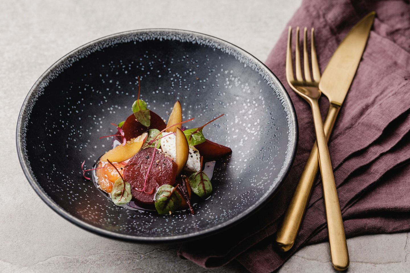 Lukewarm beets with caramelized plums and fresh goat's cheese in a black deep plate with gold cutlery
