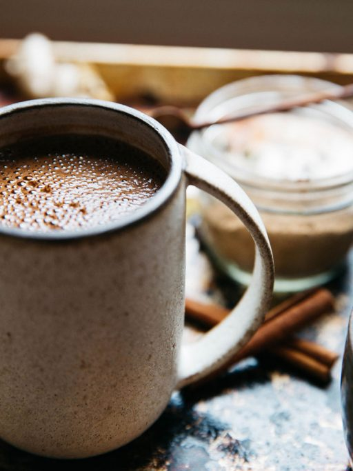 A cup of coffee with cinnamon sticks on a table
