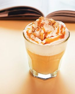 a cup of milky coffee with whipped milk in a glass besides an open book