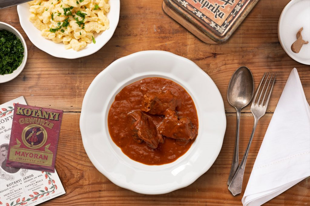 A plate full of goulash and a small bowl of spaetzle arranged on a dark wooden table.