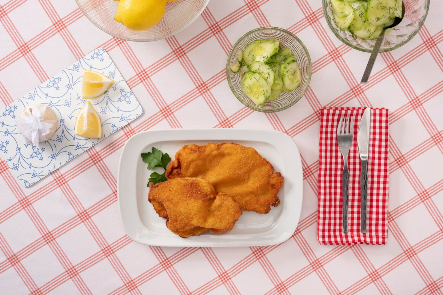 Two Wiener Schnitzel served with a cucumber salad garnished with dill.